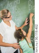 Купить «Teacher assisting schoolgirl to learn alphabet on chalkboard in classroom», фото № 30119402, снято 10 апреля 2016 г. (c) Wavebreak Media / Фотобанк Лори