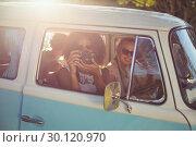 Купить «Woman taking photograph while travelling in campervan», фото № 30120970, снято 20 июля 2016 г. (c) Wavebreak Media / Фотобанк Лори