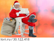 Купить «Smiling Santa showing book against blurry red background», фото № 30122418, снято 23 ноября 2016 г. (c) Wavebreak Media / Фотобанк Лори