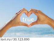 Купить «Hands forming heart shape with text true», фото № 30123890, снято 1 декабря 2016 г. (c) Wavebreak Media / Фотобанк Лори