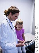 Купить «Doctor showing medical report in digital tablet to patient», фото № 30124174, снято 5 ноября 2016 г. (c) Wavebreak Media / Фотобанк Лори