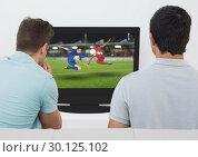 Rear view of men watching football match on television. Стоковое фото, агентство Wavebreak Media / Фотобанк Лори