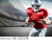 American football player holding ball while playing in pitch. Стоковое фото, агентство Wavebreak Media / Фотобанк Лори