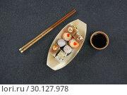 Купить «Sushi on boat shaped plate with chopsticks», фото № 30127978, снято 8 декабря 2016 г. (c) Wavebreak Media / Фотобанк Лори