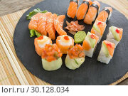 Купить «Slate tray of assorted sushi kept on mat», фото № 30128034, снято 8 декабря 2016 г. (c) Wavebreak Media / Фотобанк Лори