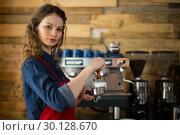 Купить «Waitress using a tamper to press ground coffee into a portafilter», фото № 30128670, снято 12 октября 2016 г. (c) Wavebreak Media / Фотобанк Лори