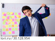 Купить «Young handsome employee in front of whiteboard with to-do list», фото № 30128954, снято 16 октября 2018 г. (c) Elnur / Фотобанк Лори