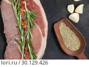 Купить «Sirloin chop, garlic and spices on black slate plate», фото № 30129426, снято 20 сентября 2016 г. (c) Wavebreak Media / Фотобанк Лори