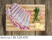 Купить «Beef ribs, rosemary herb, salt and lemon on wooden board», фото № 30129470, снято 20 сентября 2016 г. (c) Wavebreak Media / Фотобанк Лори