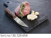 Купить «Sirloin chop, knife and garlic on slate plate», фото № 30129654, снято 20 сентября 2016 г. (c) Wavebreak Media / Фотобанк Лори