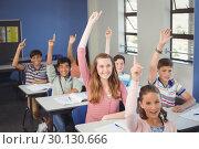 Купить «School kids raising hand in classroom at school», фото № 30130666, снято 19 ноября 2016 г. (c) Wavebreak Media / Фотобанк Лори