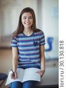 Купить «Portrait of schoolgirl sitting on bench and writing on book in classroom», фото № 30130818, снято 20 ноября 2016 г. (c) Wavebreak Media / Фотобанк Лори