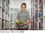 Купить «Portrait of happy schoolboy holding book in library», фото № 30131066, снято 20 ноября 2016 г. (c) Wavebreak Media / Фотобанк Лори