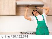 Купить «Young contractor repairing air-conditioner in kitchen», фото № 30132674, снято 31 октября 2018 г. (c) Elnur / Фотобанк Лори