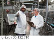 Купить «Two factory engineers discussing with each other», фото № 30132710, снято 20 октября 2016 г. (c) Wavebreak Media / Фотобанк Лори