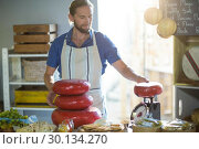 Купить «Salesman weighing gouda cheese at counter», фото № 30134270, снято 4 октября 2016 г. (c) Wavebreak Media / Фотобанк Лори
