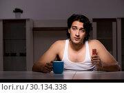 Купить «Young man suffering at home night time», фото № 30134338, снято 15 ноября 2018 г. (c) Elnur / Фотобанк Лори