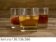 Купить «Three glasses of whiskey with ice cube», фото № 30136586, снято 11 января 2017 г. (c) Wavebreak Media / Фотобанк Лори