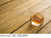 Купить «Glass of whisky on wooden table», фото № 30136990, снято 11 января 2017 г. (c) Wavebreak Media / Фотобанк Лори