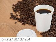 Купить «Coffee beans and black coffee in disposable cup», фото № 30137254, снято 6 октября 2016 г. (c) Wavebreak Media / Фотобанк Лори