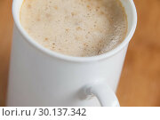 Close-up of white mug of coffee with creamy froth. Стоковое фото, агентство Wavebreak Media / Фотобанк Лори