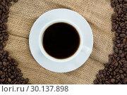 Купить «Coffee cup with coffee beans arranged on sack», фото № 30137898, снято 6 октября 2016 г. (c) Wavebreak Media / Фотобанк Лори