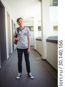 Купить «Smiling schoolboy standing with schoolbag in corridor at school», фото № 30140166, снято 19 ноября 2016 г. (c) Wavebreak Media / Фотобанк Лори