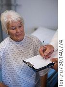 Купить «Doctor writing medical details of a senior patient», фото № 30140774, снято 5 декабря 2016 г. (c) Wavebreak Media / Фотобанк Лори