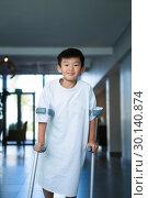 Купить «Boy patient walking with crutches in corridor», фото № 30140874, снято 5 декабря 2016 г. (c) Wavebreak Media / Фотобанк Лори