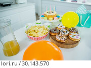 Купить «Doughnuts, potato chip, birthday cake and balloons on table», фото № 30143570, снято 29 ноября 2016 г. (c) Wavebreak Media / Фотобанк Лори