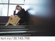 Купить «Depressed businesswoman sitting on stairs holding cardboard sheet with text need work», фото № 30143798, снято 19 ноября 2016 г. (c) Wavebreak Media / Фотобанк Лори