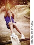 Купить «Fit man hanging on rope during obstacle course», фото № 30147362, снято 24 ноября 2016 г. (c) Wavebreak Media / Фотобанк Лори