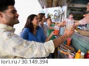 Купить «Waitress and waiter giving juice to customer at counter», фото № 30149394, снято 26 марта 2017 г. (c) Wavebreak Media / Фотобанк Лори