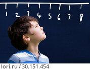 Купить «Boy looking up with ruler numbers on blackboard», фото № 30151454, снято 24 июля 2017 г. (c) Wavebreak Media / Фотобанк Лори