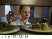 Купить «Female chef reading order», фото № 30153186, снято 22 августа 2017 г. (c) Wavebreak Media / Фотобанк Лори