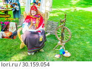 Russia Samara August 2018: Flower Festival. Historical reconstruction. A grandmother in a Russian national costume reads fairy tales in the interior of rural life. Редакционное фото, фотограф Акиньшин Владимир / Фотобанк Лори
