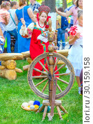 Купить «Russia Samara August 2018: Flower Festival. Historical reconstruction of rural life. The girl in the Russian national costume is engaged in embroidery. Nearby there is a spinning wheel with threads.», фото № 30159158, снято 25 августа 2018 г. (c) Акиньшин Владимир / Фотобанк Лори
