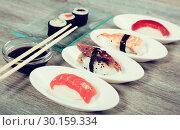 Купить «four kinds Nigirisushi on oval saucers and makizushi», фото № 30159334, снято 25 октября 2016 г. (c) Татьяна Яцевич / Фотобанк Лори