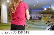 Купить «Playing mini golf. A young woman playing mini golf indoors. Hitting the ball and putting the stick on the shoulder», видеоролик № 30159618, снято 25 марта 2019 г. (c) Константин Шишкин / Фотобанк Лори
