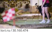 Купить «A young woman playing mini golf. A woman hitting the golf balls several times», видеоролик № 30160474, снято 25 марта 2019 г. (c) Константин Шишкин / Фотобанк Лори
