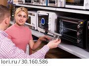 Купить «couple choosing new modern mini oven», фото № 30160586, снято 1 марта 2018 г. (c) Яков Филимонов / Фотобанк Лори