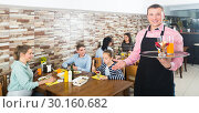 Waiter showing hospitality and meeting visitors in cafe. Стоковое фото, фотограф Яков Филимонов / Фотобанк Лори