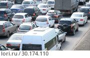 Купить «Ufa - JUL 18: Car traffic jam on the highway. A hot summer day on JULY 01, 2018 in Ufa, Russia», видеоролик № 30174110, снято 1 июля 2018 г. (c) Mikhail Erguine / Фотобанк Лори