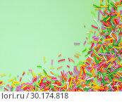 Купить «Border frame of colorful sprinkles on green background», фото № 30174818, снято 28 ноября 2016 г. (c) Ольга Сергеева / Фотобанк Лори