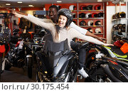 Купить «Couple sitting together on new motorcycle in store and having fun», фото № 30175454, снято 16 января 2019 г. (c) Яков Филимонов / Фотобанк Лори