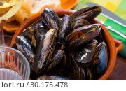 Купить «Delicious baked mussels on a bowl with onion sauce at table», фото № 30175478, снято 22 марта 2019 г. (c) Яков Филимонов / Фотобанк Лори