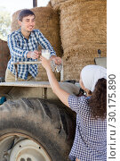 country woman give to man tractor driver glass of milk on farm. Стоковое фото, фотограф Татьяна Яцевич / Фотобанк Лори