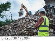 Купить «Demolition construction work. Worker at building site», фото № 30175994, снято 14 июля 2018 г. (c) Дмитрий Калиновский / Фотобанк Лори