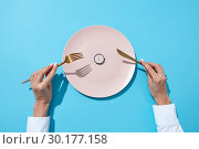 White plate with round whatch shows six o'clock served knife and fork in a girl's hands on a blue background. Time to eat and diet concept. Top view. Стоковое фото, фотограф Ярослав Данильченко / Фотобанк Лори