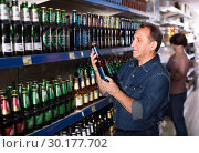 Pensioner selecting a beer at the store. Стоковое фото, фотограф Яков Филимонов / Фотобанк Лори